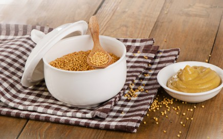 Mustard seeds and sauce on a wooden background.