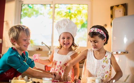 Three brother and sisters are smiling, cooking together in a luminous kitchen. They are standing close to each other at a wooden table, working on a spread pastry in order to make small cakes.